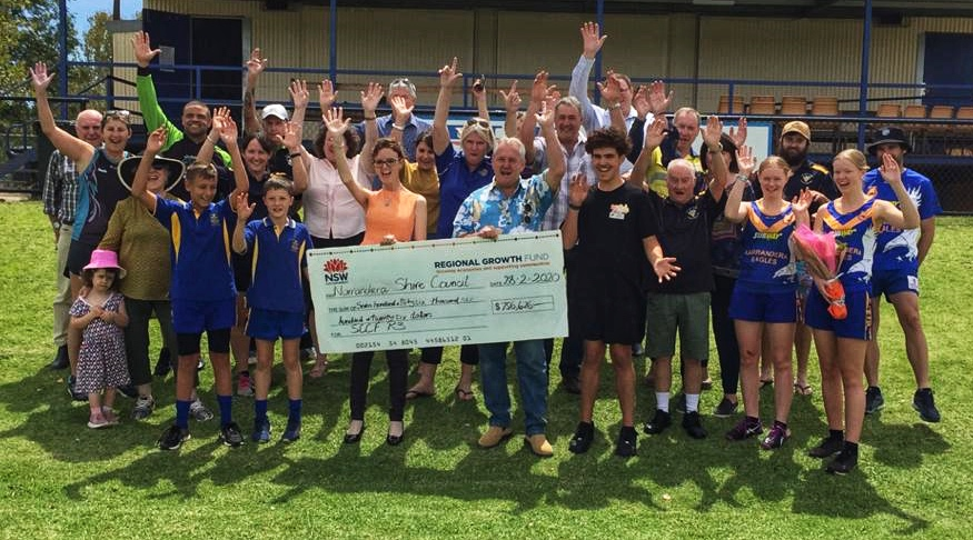 Steph Cooke is surrounded by a group of people smiling and jumping in the air with their hands up. The hold a large cheque at the front of the photo.