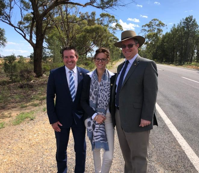 Paul Toole, Steph Cooke and Rick Firman stand close together next to a road in Temora Shire.