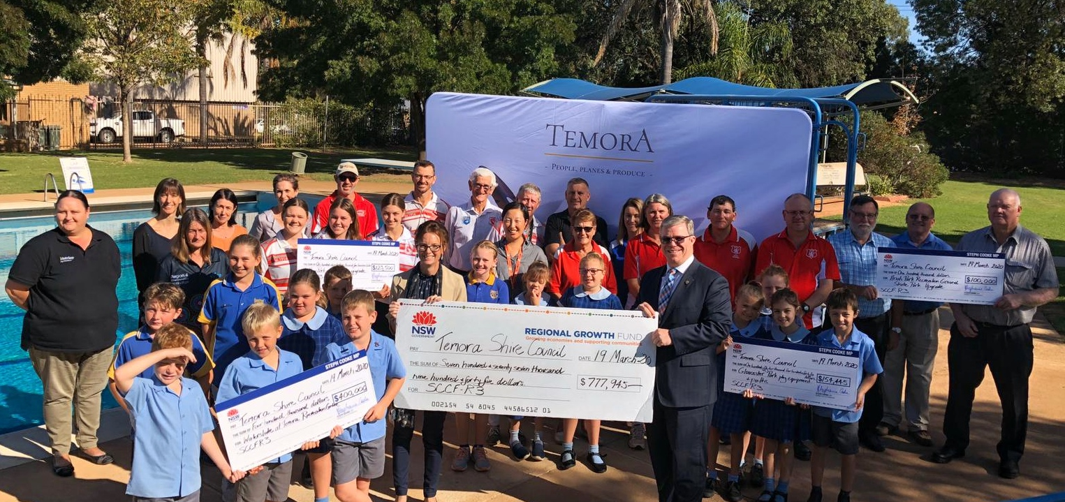 A large group of people stand with novelty cheques next to Temora Pool.