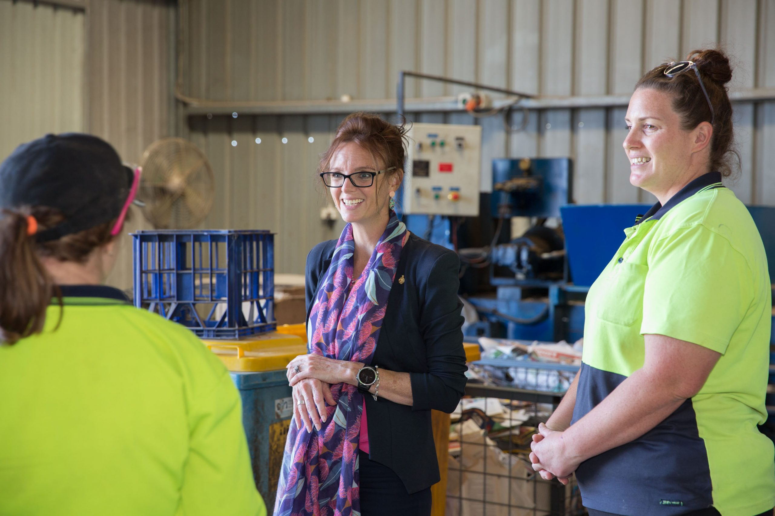 Steph Cooke with two Kurrajong employees in high-visibility clothing stand near large containers of cardboard and recyclable materials.