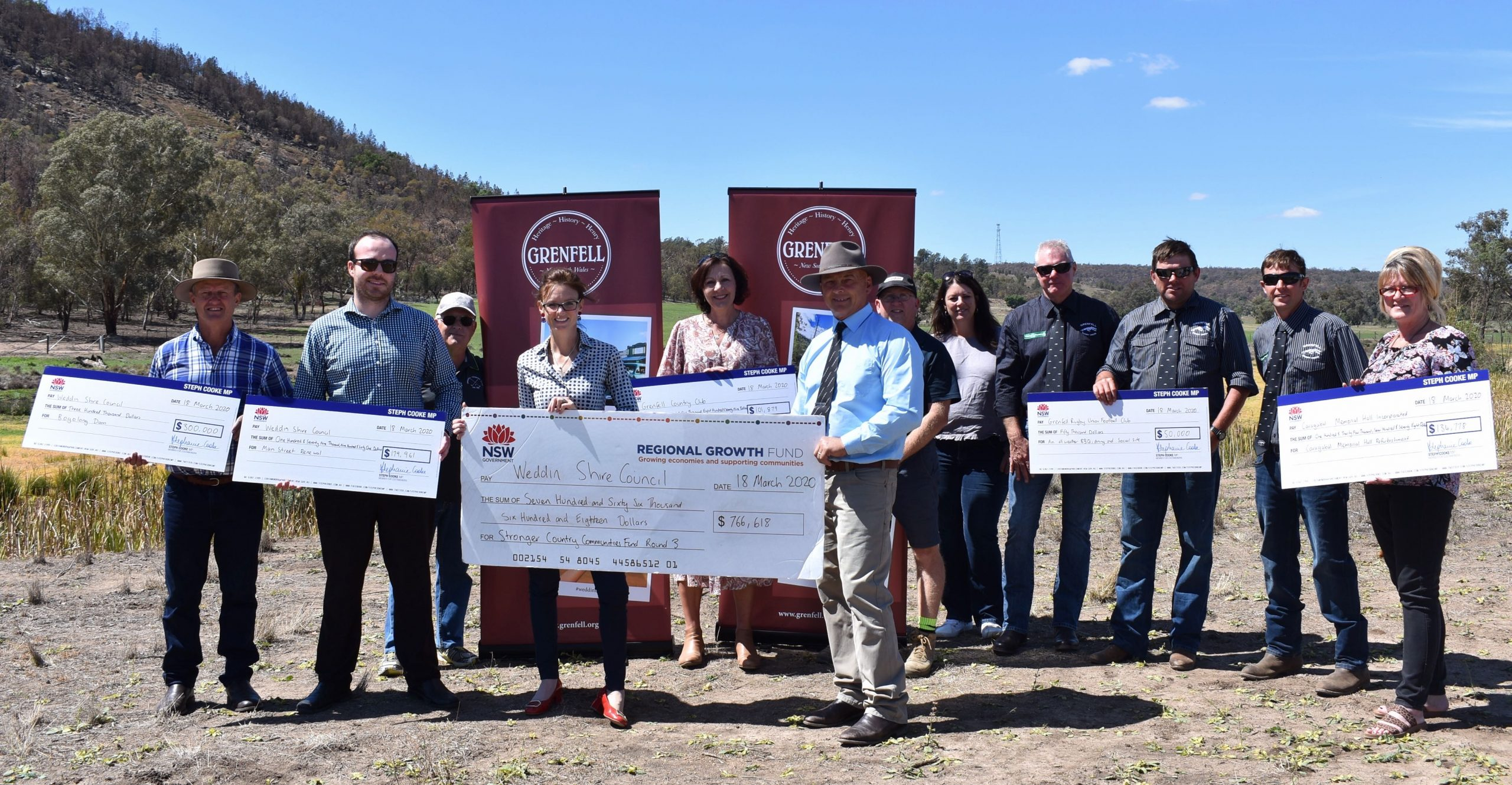 Members of the Weddin community hold six novelty-sized cheques for projects on the banks of Bogolong Dam.