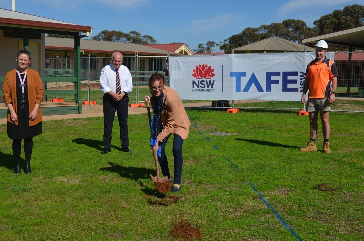 TAFE Services Co-ordinator Kate Braunberger, Bland Shire General Manager Ray Smith and Joss representative Sam Cross stand at a distance from Steph Cooke MP while she lifts a shovel full of dirt. They stand in front of a metal construction fence and a TAFE NSW banner.