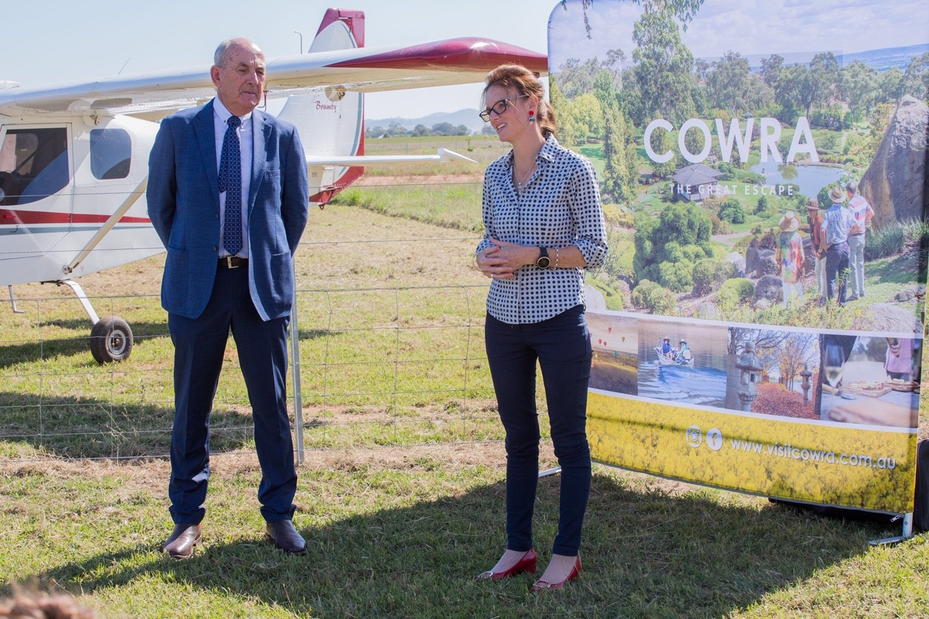 Mayor of Cowra Bill West and Steph Cooke stand on patchy grass in front of a Cowra banner and near a small red and white areoplane.