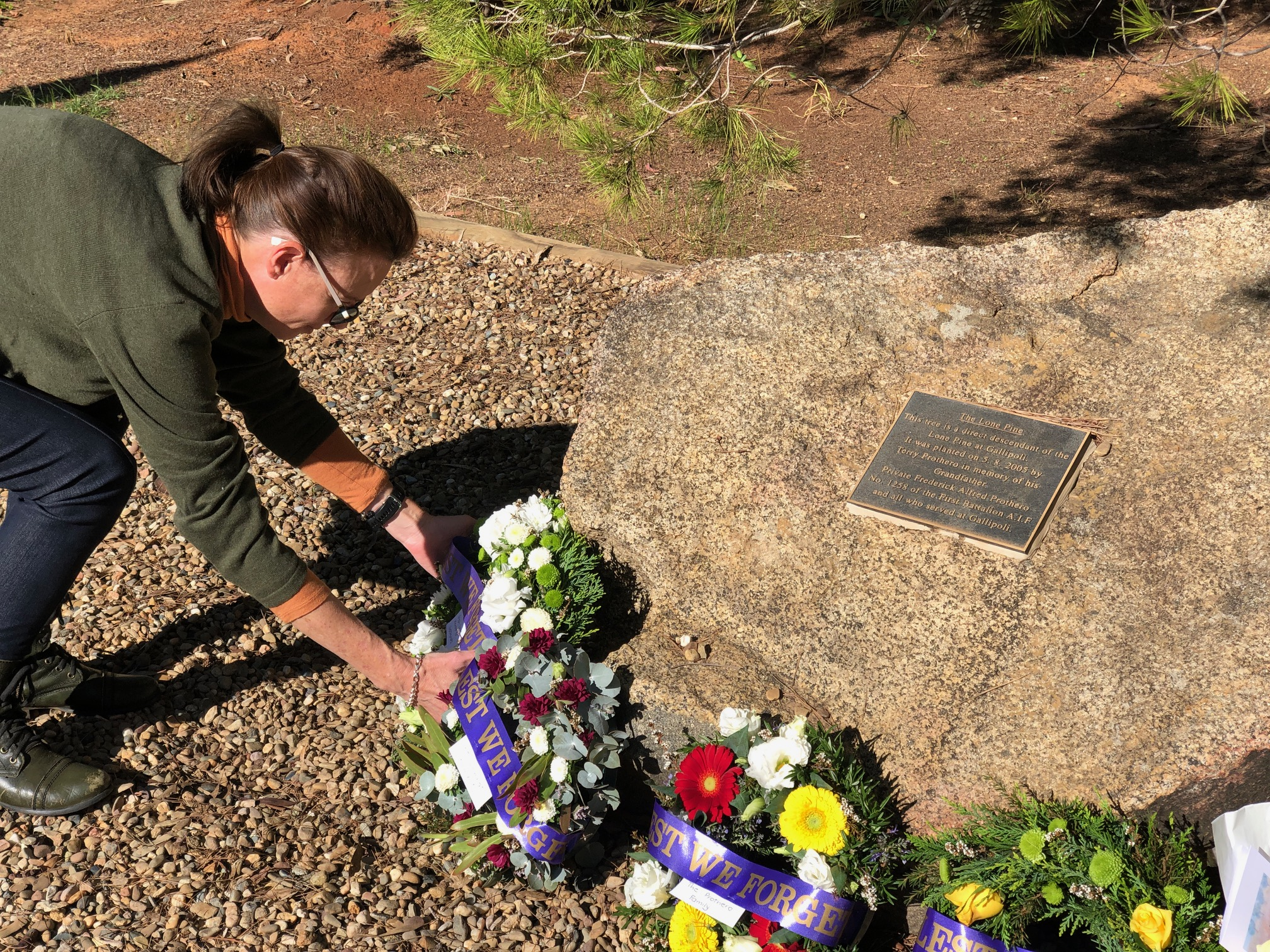 Steph Cooke places a wreath at a stone with a plaque identifying the Wombat Lone Pine.