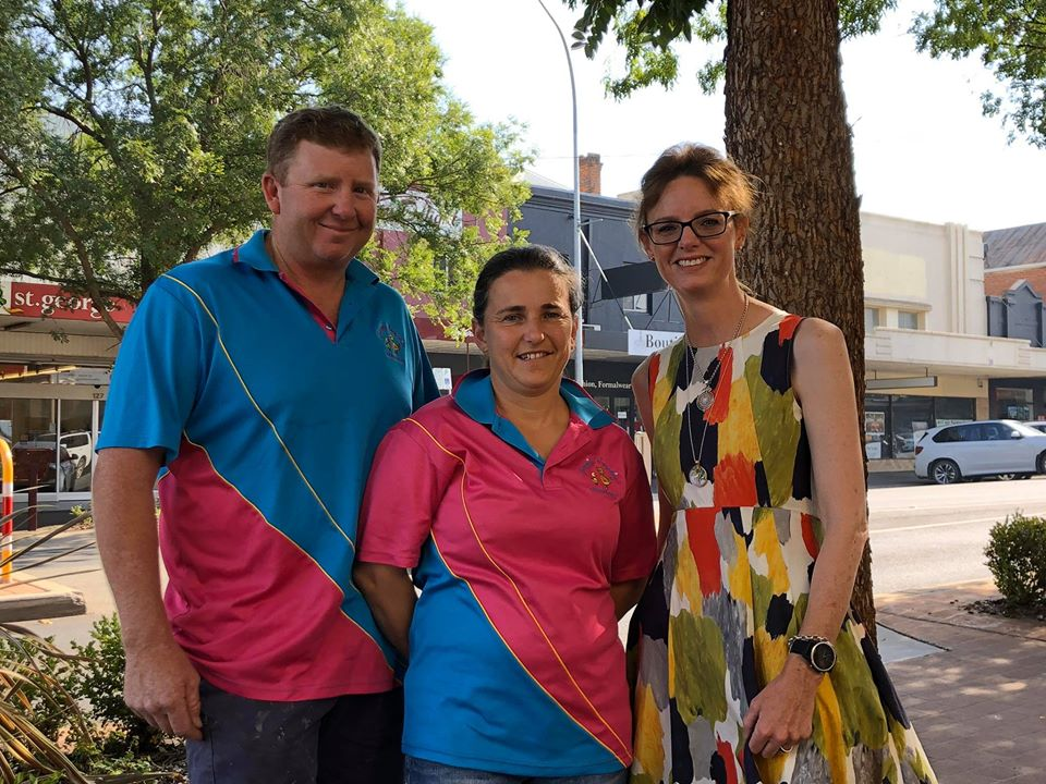 Peter and Emma Cockburn wear blue and pink shirts standing next to Steph Cooke in front of a large tree and main street lined with shops.