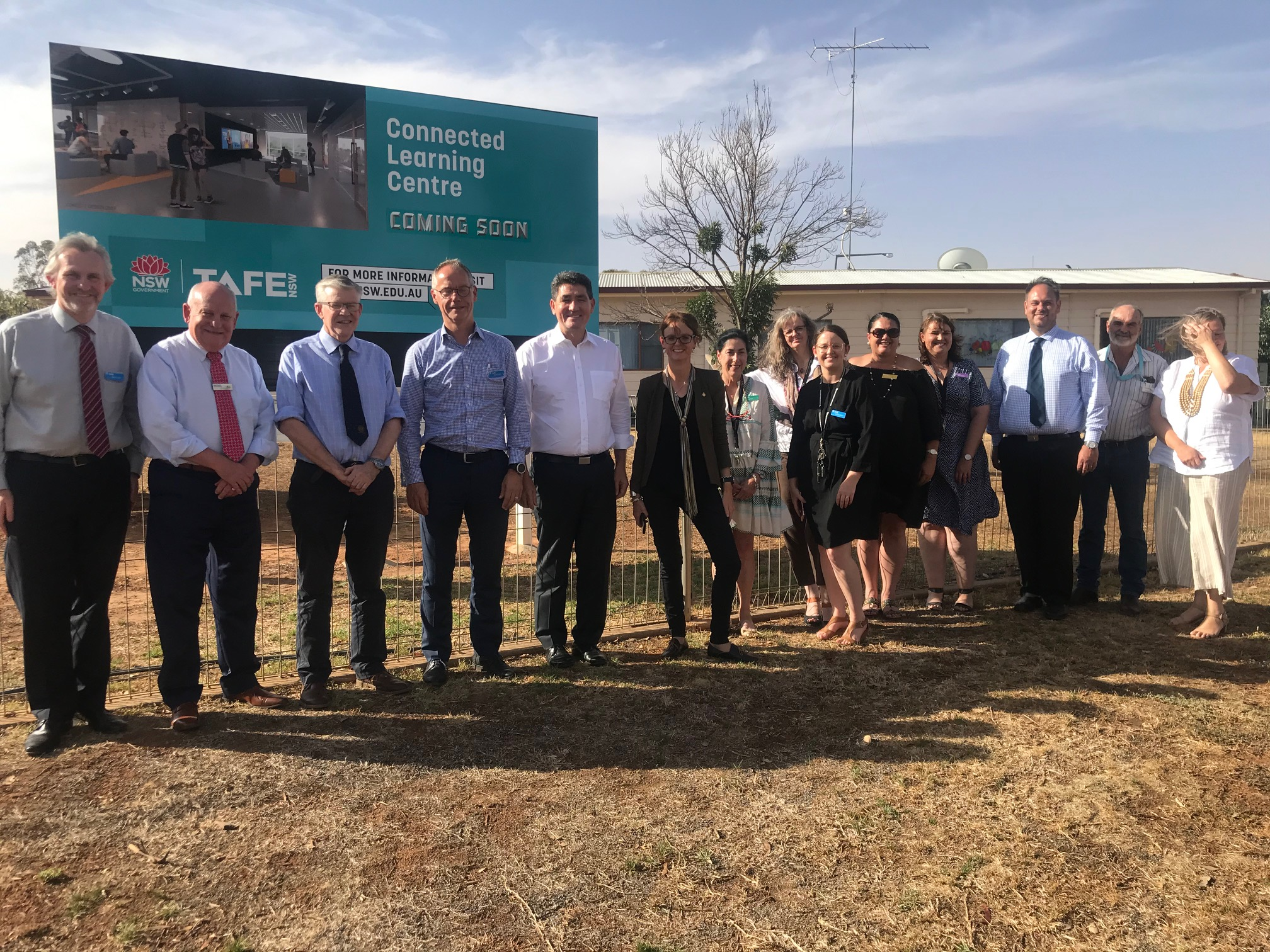 A group of people including Minister Geoff Lee and Steph Cooke stand in front of the West Wyalong TAFE.
