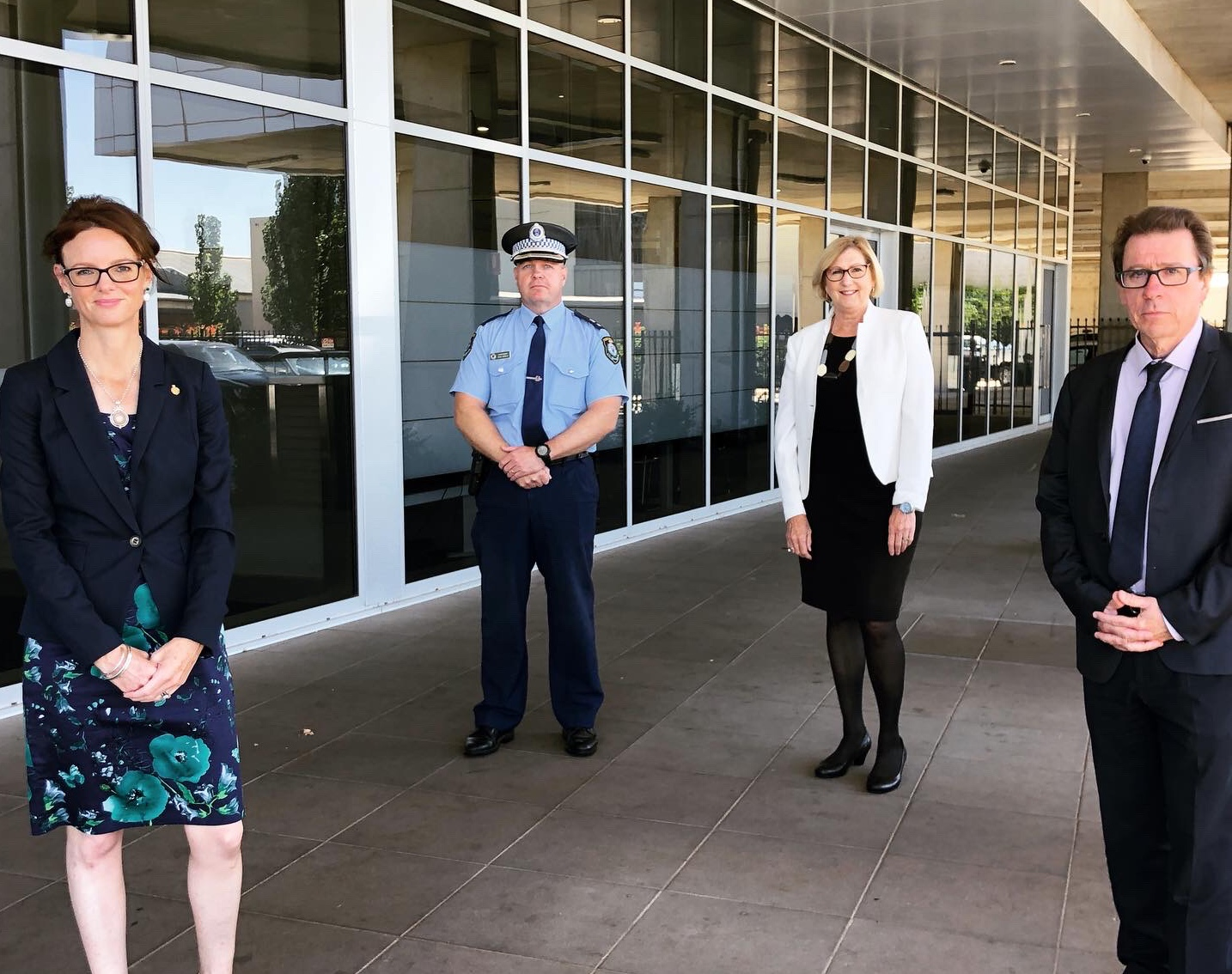 Steph Cooke, Superintendent Bob Noble, Jill Ludford and Joe McGirr stand 1.5 metres apart from each other in front of a dark glass building.