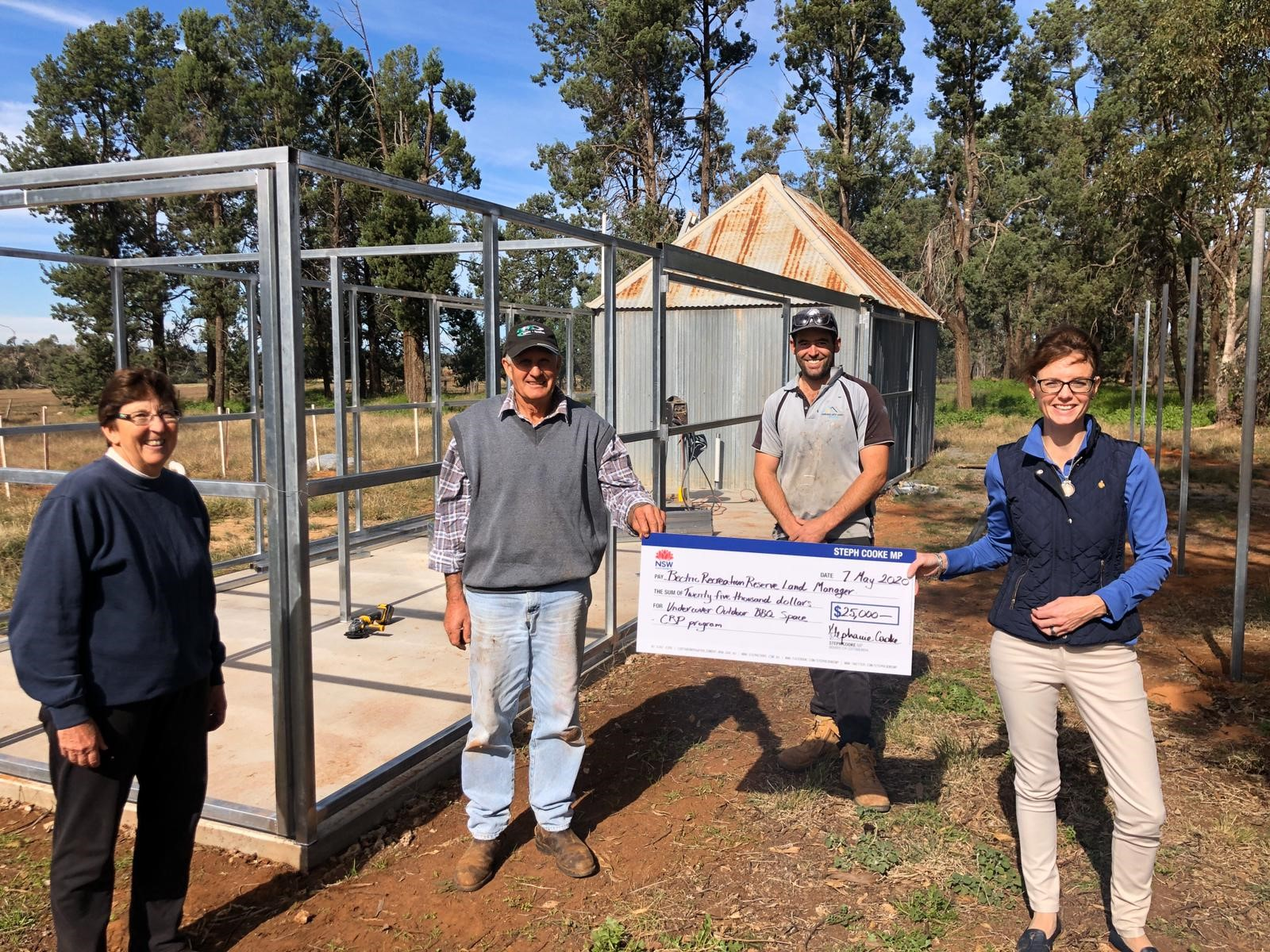 Denise  and Allan Breust, builder Nathan Stimson and Steph Cooke MP hold a large cheque in front of a metal frame and concrete slab.