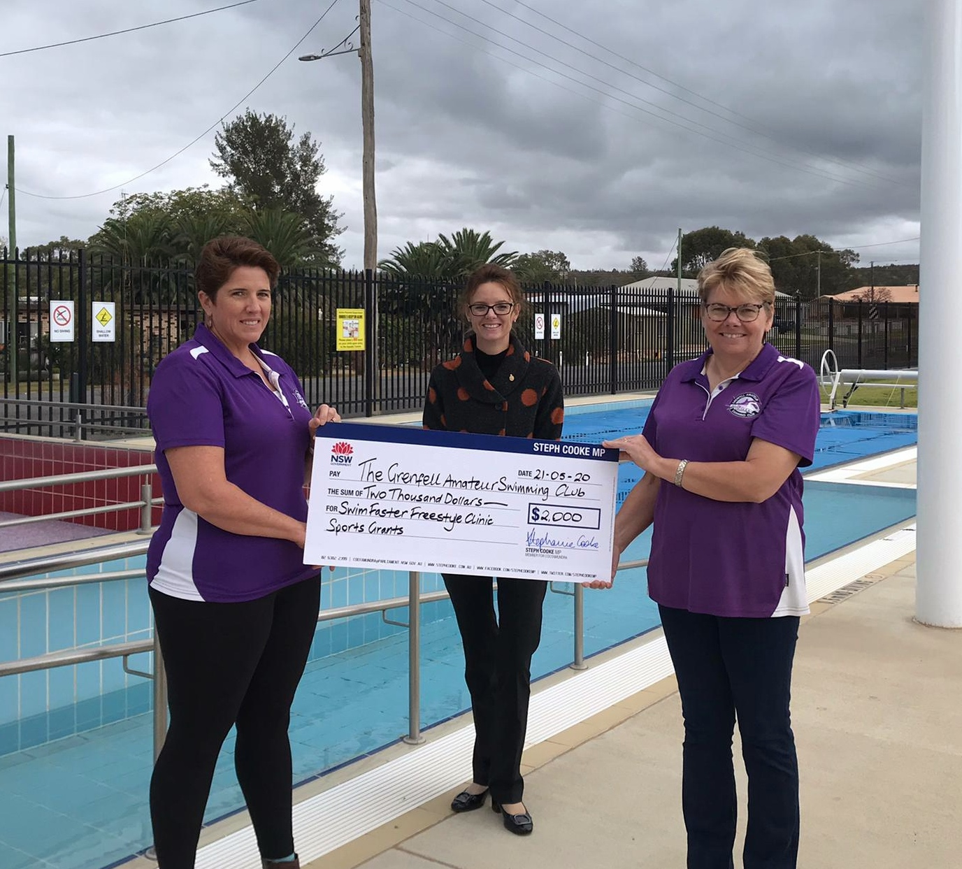 Liz Robinson, Steph Cooke MP and Nicola Mitton hold a large cheque and stand at the edge of a swimming pool. Liz and Nicola wear club shirts. All three smile at the camera.