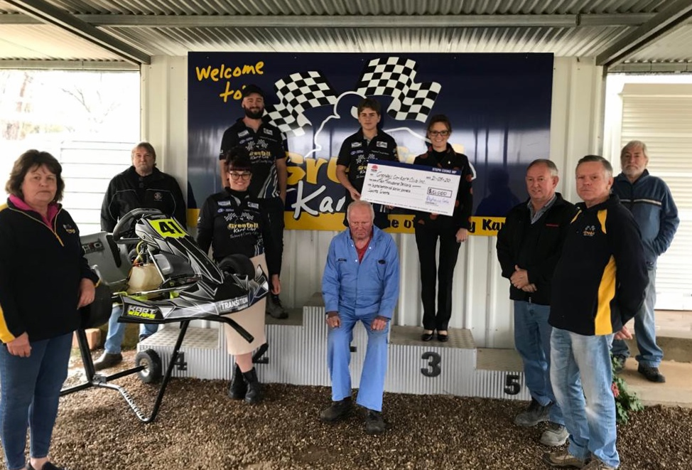 Members of the Grenfell Go Kart Club and Steph Cooke stand on a winners podium and hold a novelty cheque.
