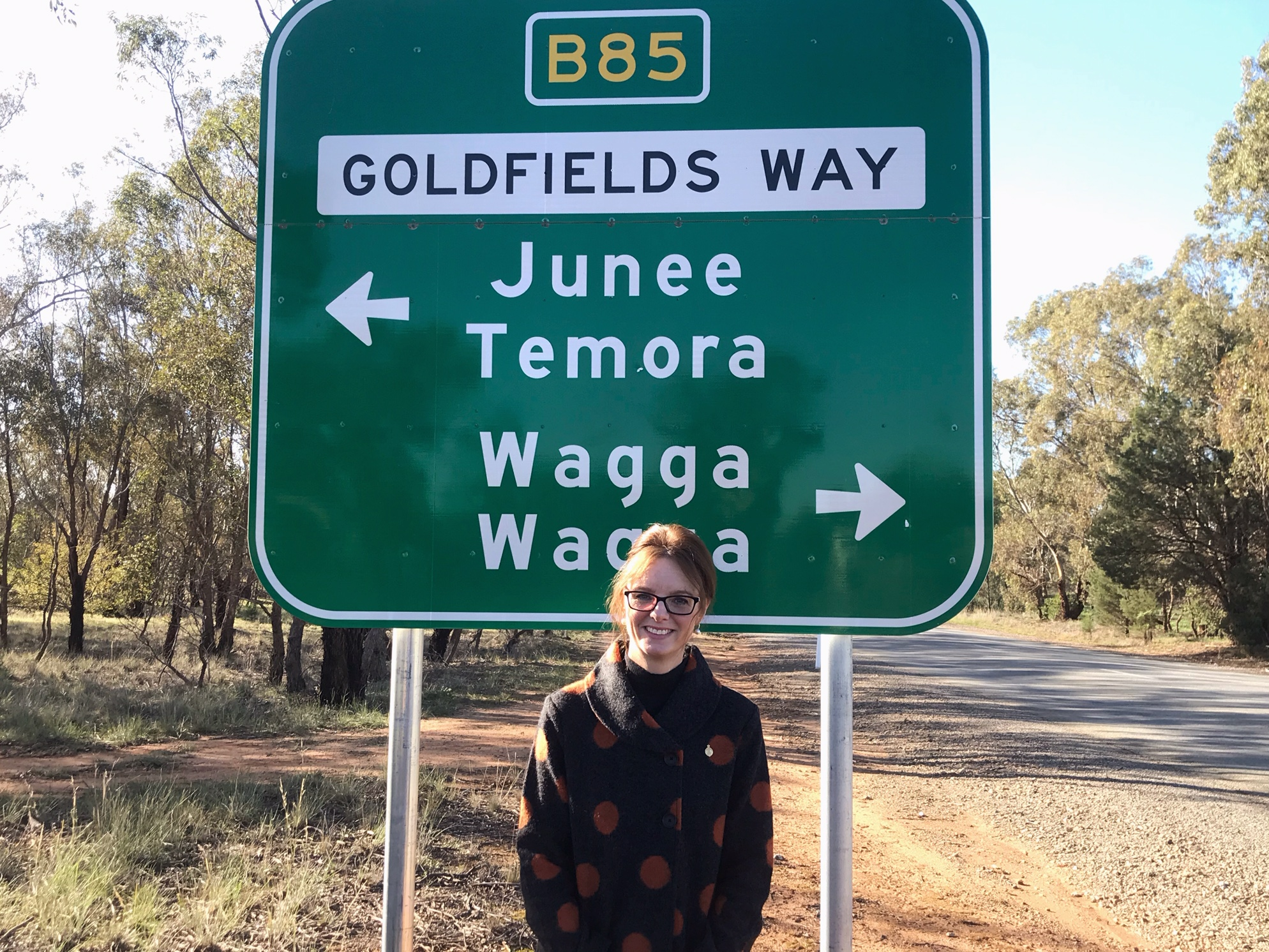 Steph Cooke stands in front of a sign for the Goldenfields Way telling the direction to Wagga Wagga, Temora and Junee.