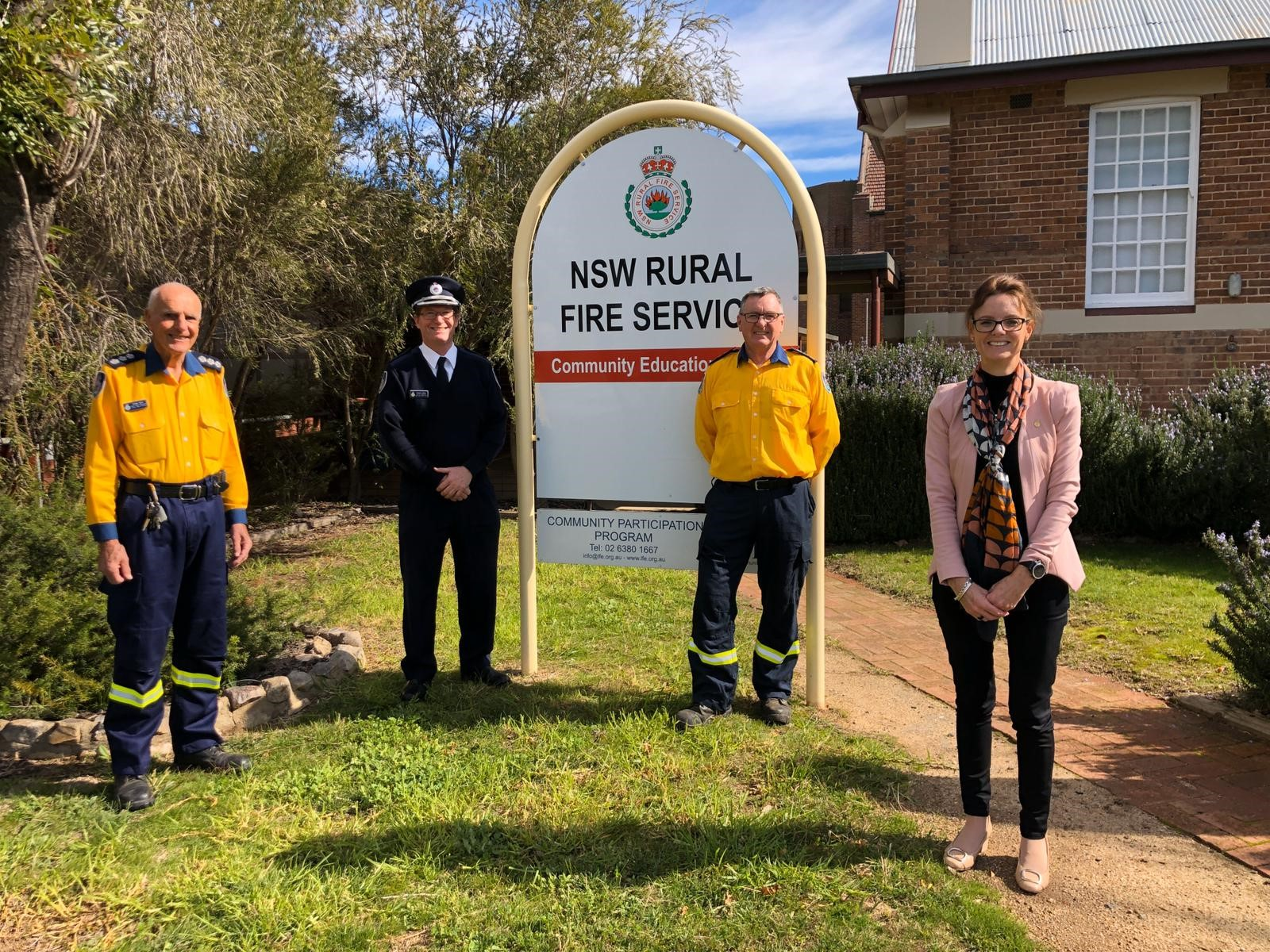 Group Captain Phillip Baer, APM, AFSM, Superintendent Andrew Dillon, Group Captain Peter Holding, AFSM and Member for Cootamundra Steph Cooke stand in front of an RFS sign.