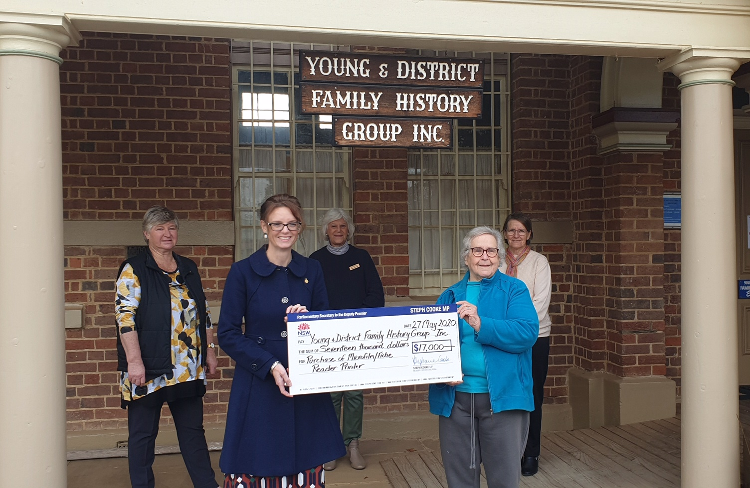 Kay McDonald, Steph Cooke MP, Margaret Hall, Carmel Price and Mary Murray hold a large cheque and stand under the sign for the Young & District Family History Group Inc.