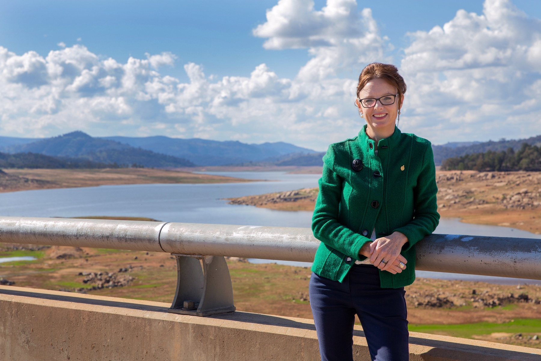 Steph Cooke leans on the rail at the Wyangala Dam and looks at the camera. The Dam is behind her and the water level is visibly low.