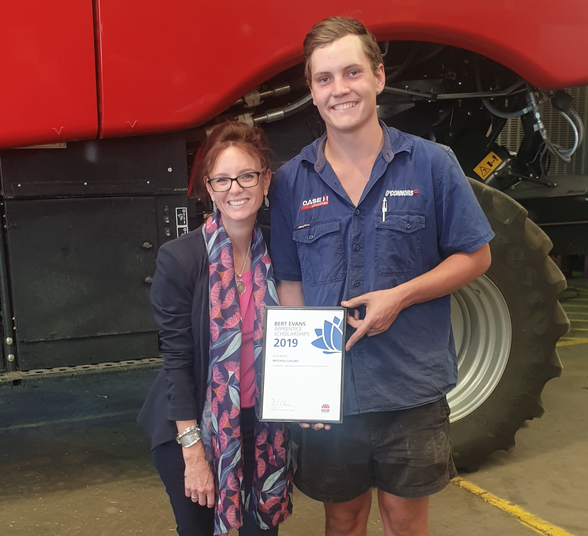Steph Cooke and Mitchell Collins stand close together and smile at the camera. Mitchell holds his scholarship certificate. They stand in front of a large red header.