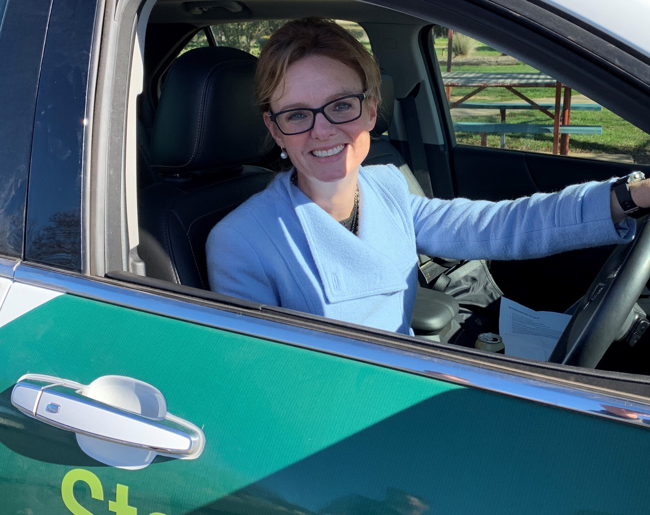 Steph Cooke smiling in her car on side of road.