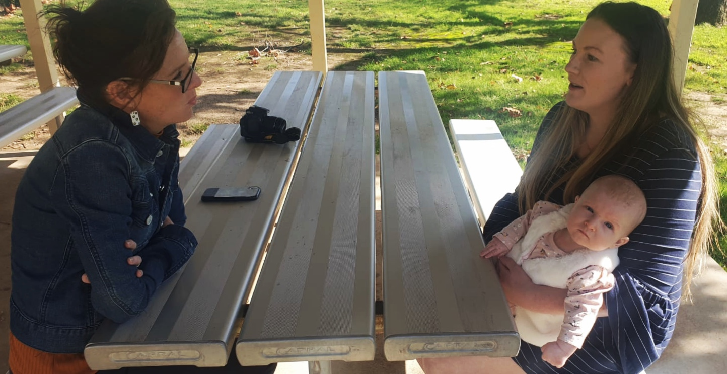 Steph Cooke and Lisa Stocks sit across a metal picnic table chatting. Lisa holds her baby daughter Hallie who looks curiously at the camera.