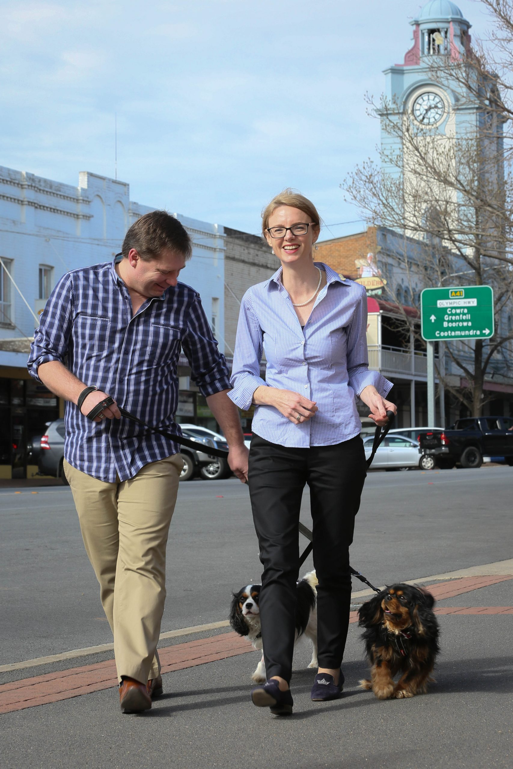 Keith Duran and Member for Cootamundra Steph Cooke walk their dogs down the main street of Young smiling