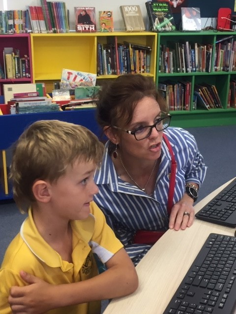 Steph Cooke and a school student look at a computer together.