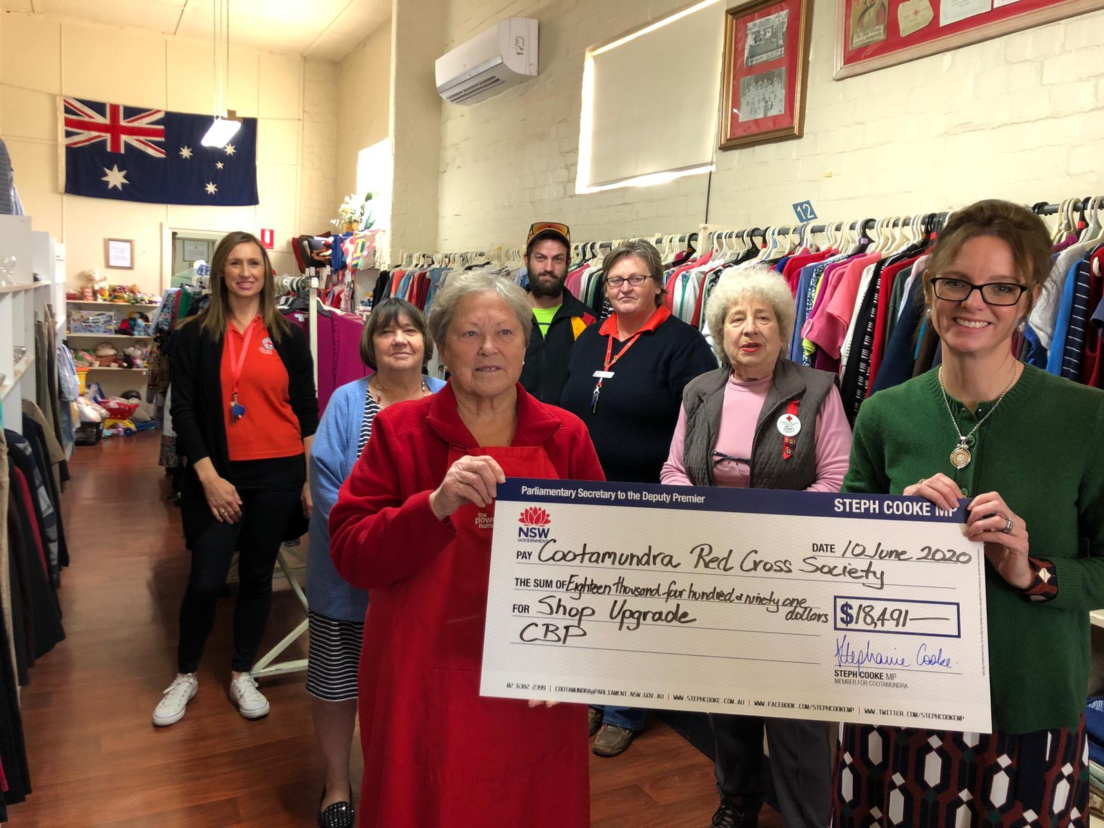 Megan Norton, Lois Jordan, Helen Ecckleston, Aaron Moore, Colina Meadows, Betti Punnett and Steph Cooke stand in front of a large rack of clothes and hold a novelty cheque.