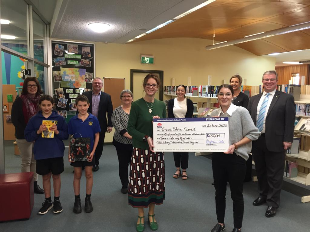 Steph Cooke MP hands a cheque to Branch Librarian Wendy Manning, with members of the Temora Shire Council and library community standing around them. They stand in the library with shelves filled with books behind them.