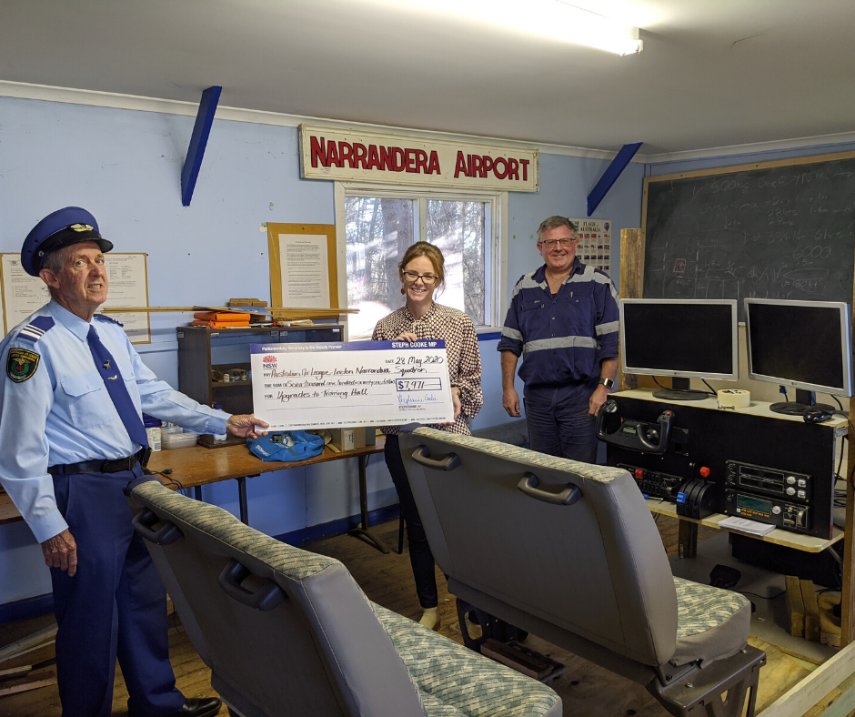 """Squadron Leader Captain Bob Manning in uniform of the local Air League Squadron receives a large cheque for $7,971 from Member for Cootamundra Steph Cooke MP watched on by Member of Narrandera Leeton Australian Air League Craig Day (Pilot Trainer).  A """"home-made"""" flight simulator for training purposes is in the foreground"""