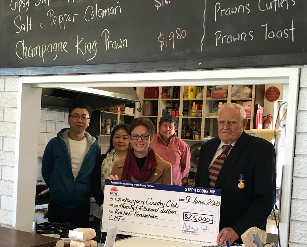 Chef Arthur Chaw, Chef Sophie Sim, Steph Cooke, Lloyd Jackson and Ted Thompson hold a large cheque and stand in the kitchen of the Gooloogong Country Club