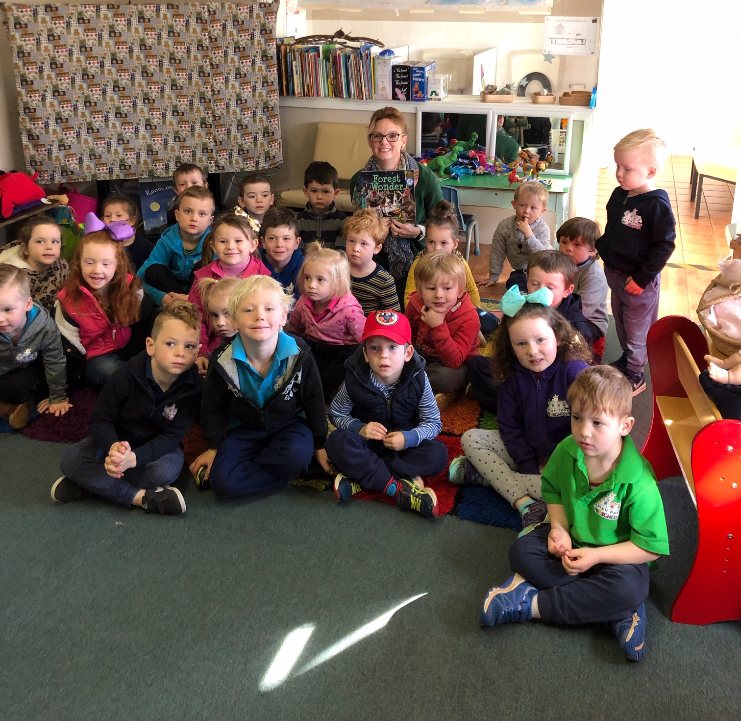 Steph Cooke sits amongst a large group of preschool students. They all look at the camera and smile. Steph is holding a picture book.