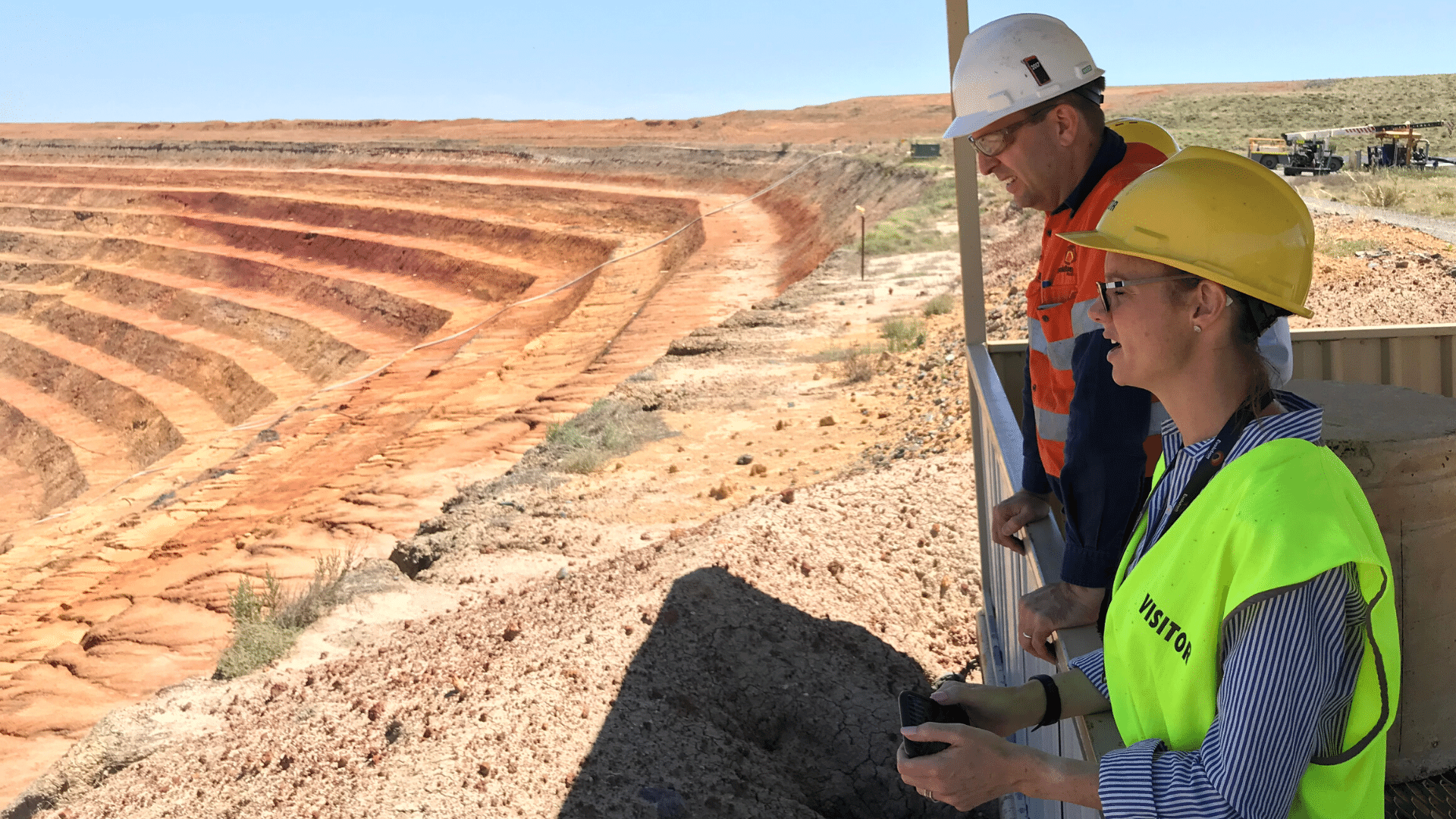 Member for Cootamundra Steph Cooke MP prior to social distancing inspects Lake Cowal Gold Mine in the Bland Shire with visitor high viz vest on and hard hat.  The golden stacked quarry is visible in the background as a mining representative also looks on beside Steph.