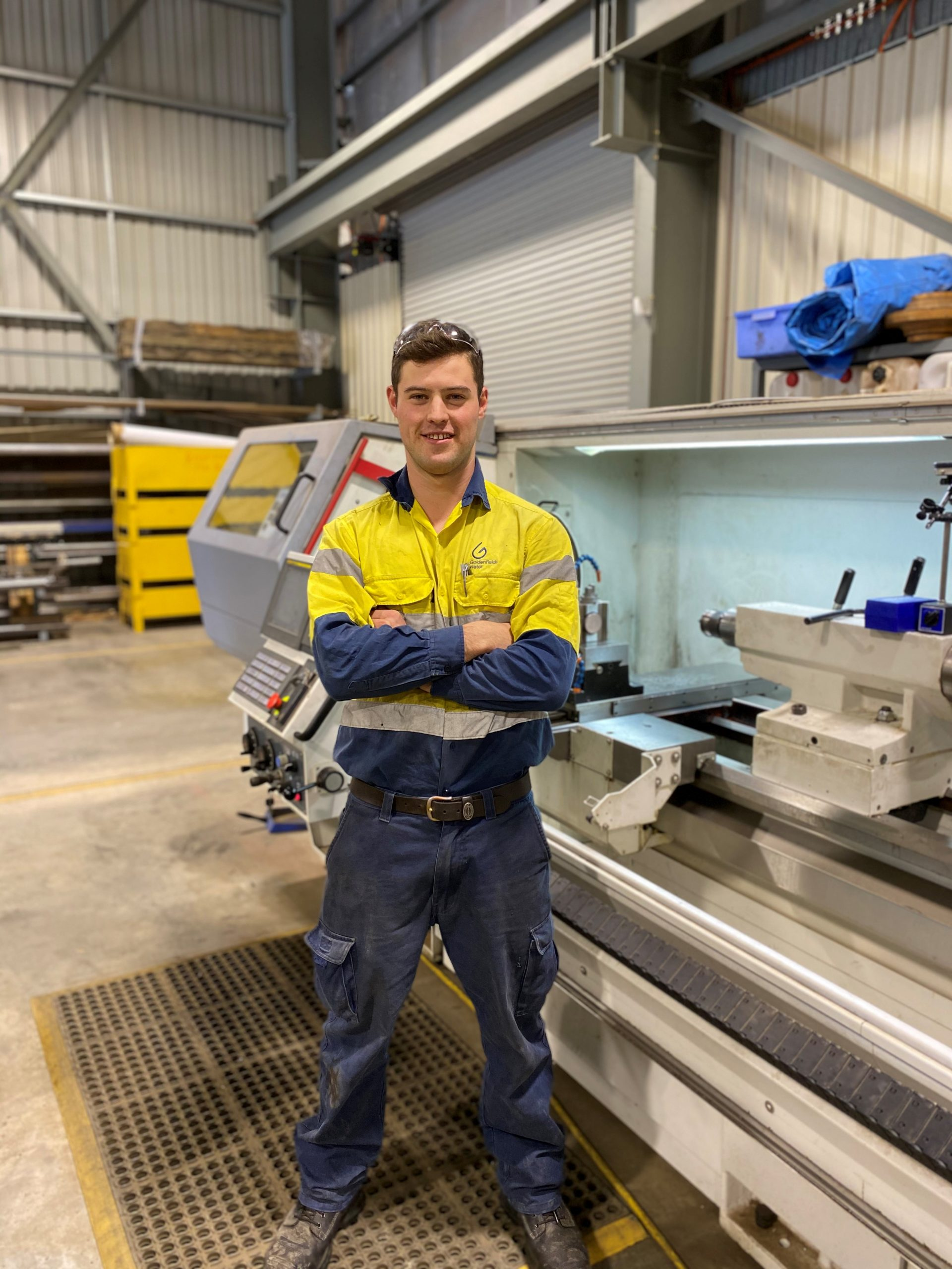 Blake Hingerty stands in a workshop, next to machinery. He is wearing high vis work clothes and stares straight at the camera with his arms crossed, smiling and with safety goggles on his head.