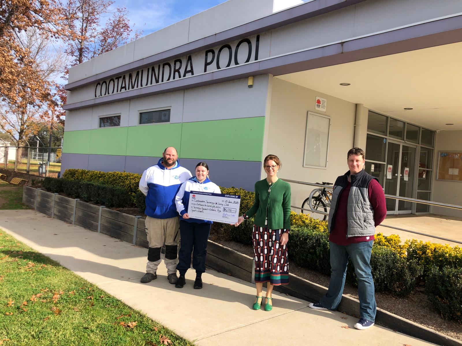 Adam Gammon, Abbey Gammon, Steph Cooke MP and Gareth Jones stand out the front of the Cootamundra Pool. They hold a large cheque between them and are standing 1.5 metres from each other.