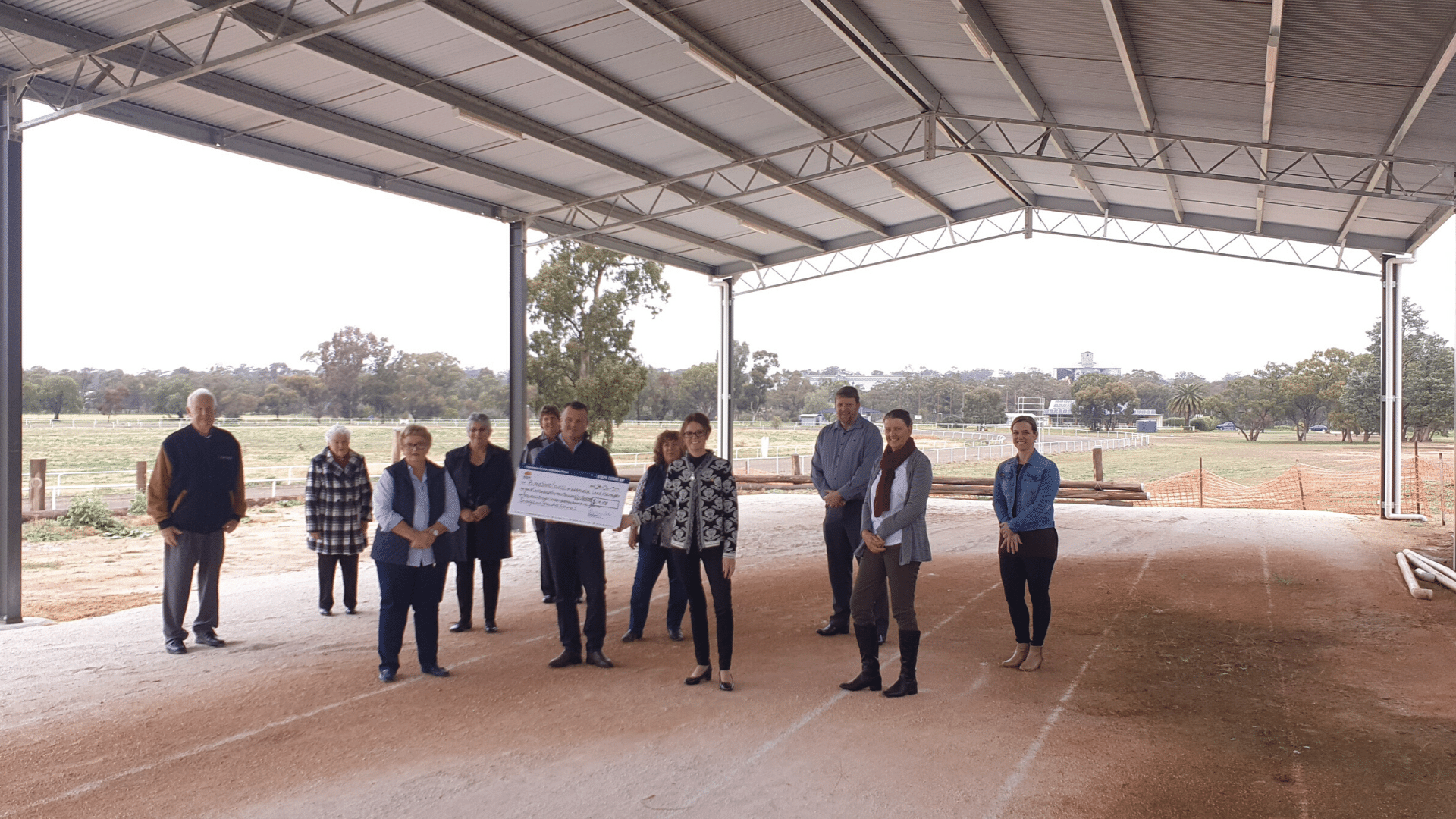 Steph Cooke MP stands in middle front row wearing a black and white coat with black pants holding a cheque with Craig Sutton, and Representatives of Weethalle community and Bland Shire Council under a large steel structure overlooking rural landscape