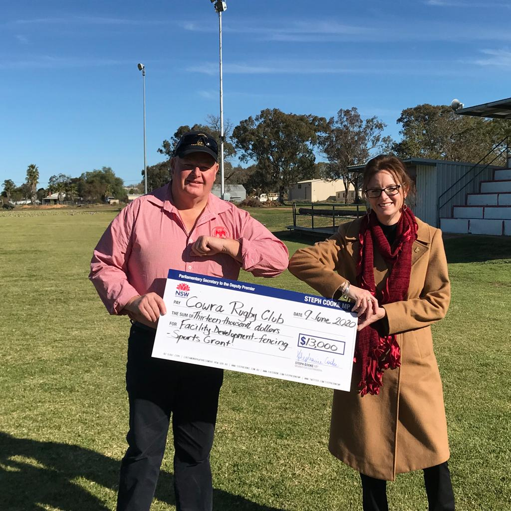 Ian Robertson and Steph Cooke MP holding a large cheque and standing on the Cowra rugby ground.