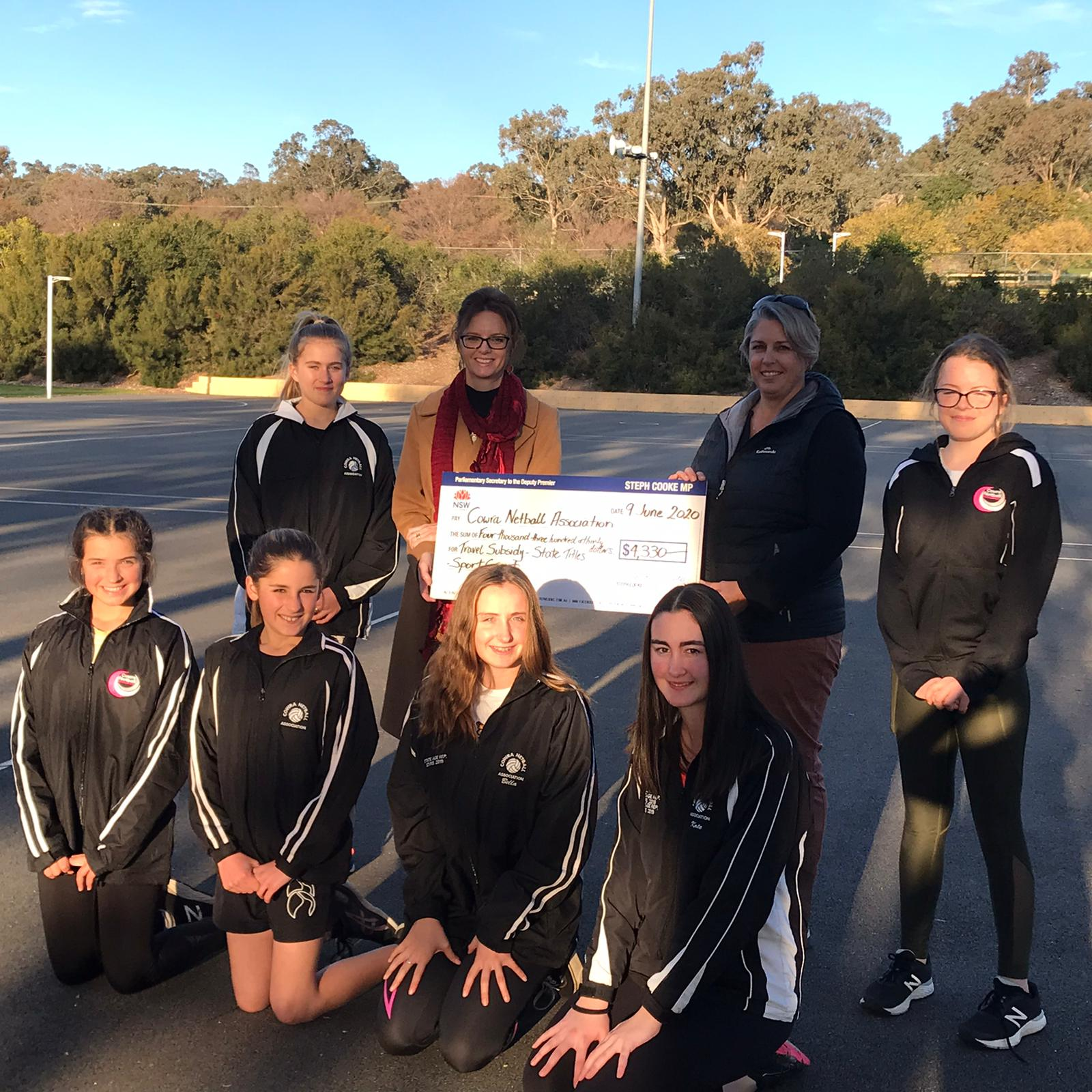 Members of the Cowra Netball Association and Steph Cooke MP holding a large cheque and standing on a netball court. There are six members of the club with Steph, all of them wear black uniforms.