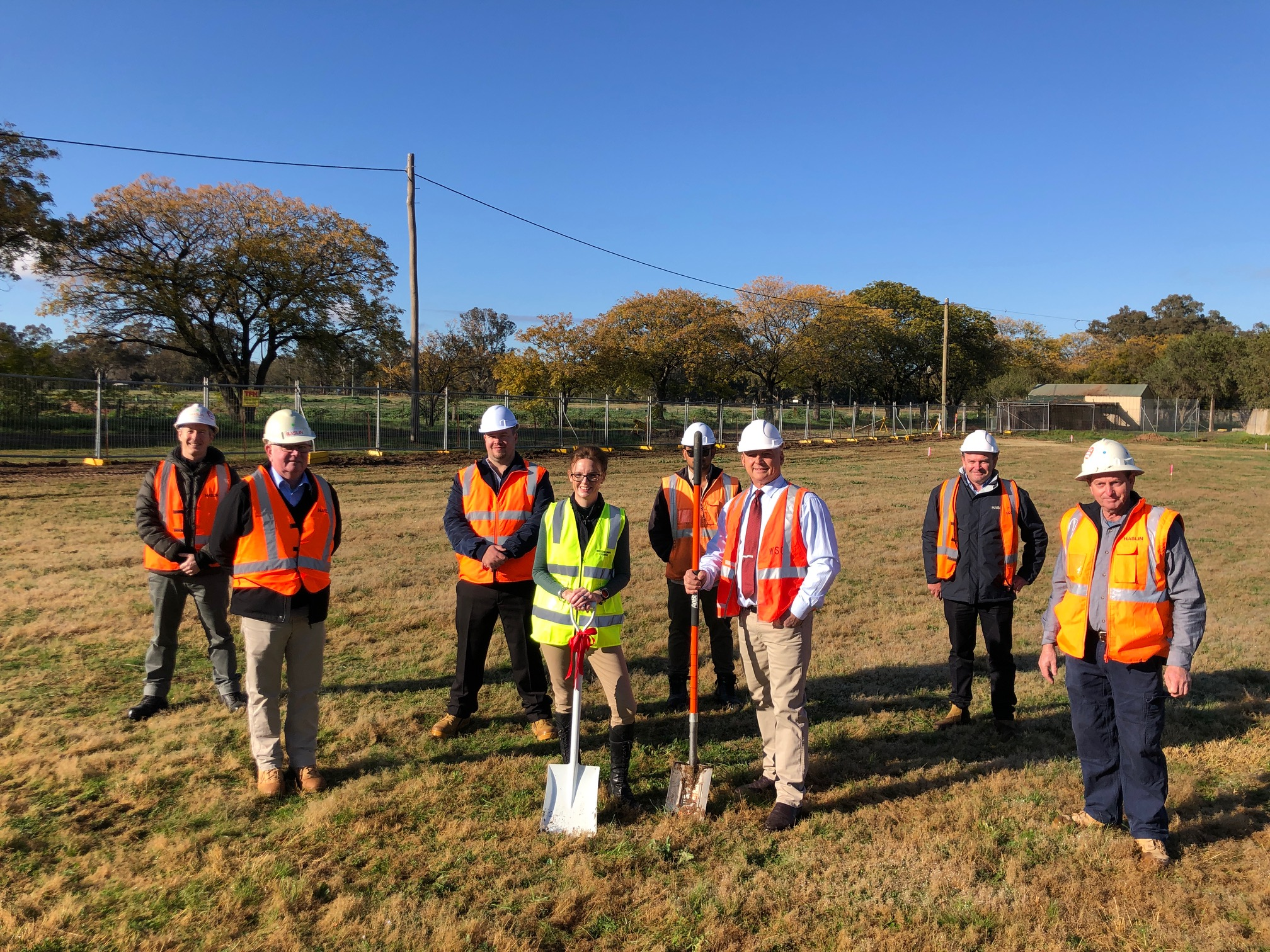 Steph Cooke stands with a group of men from the Weddin Shire Council and project contractor Haslin. Steph and the Mayor hold shovels. Everyone is wearing hi-vis vests.