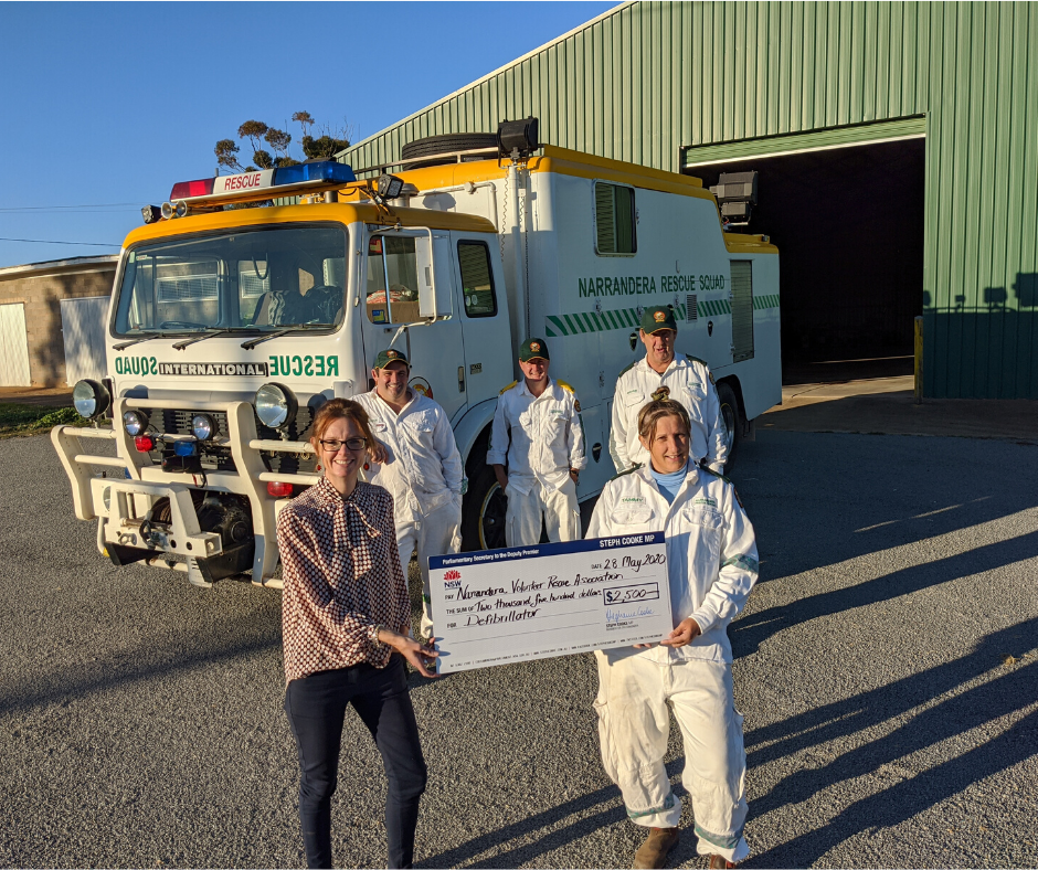 Member for Cootamundra Steph Cooke hands large cheque for $2,500 to Tammy Riddell in front of photo with other squad in uniform at rear of photo and a Narrandera Rescue Squad truck also in background
