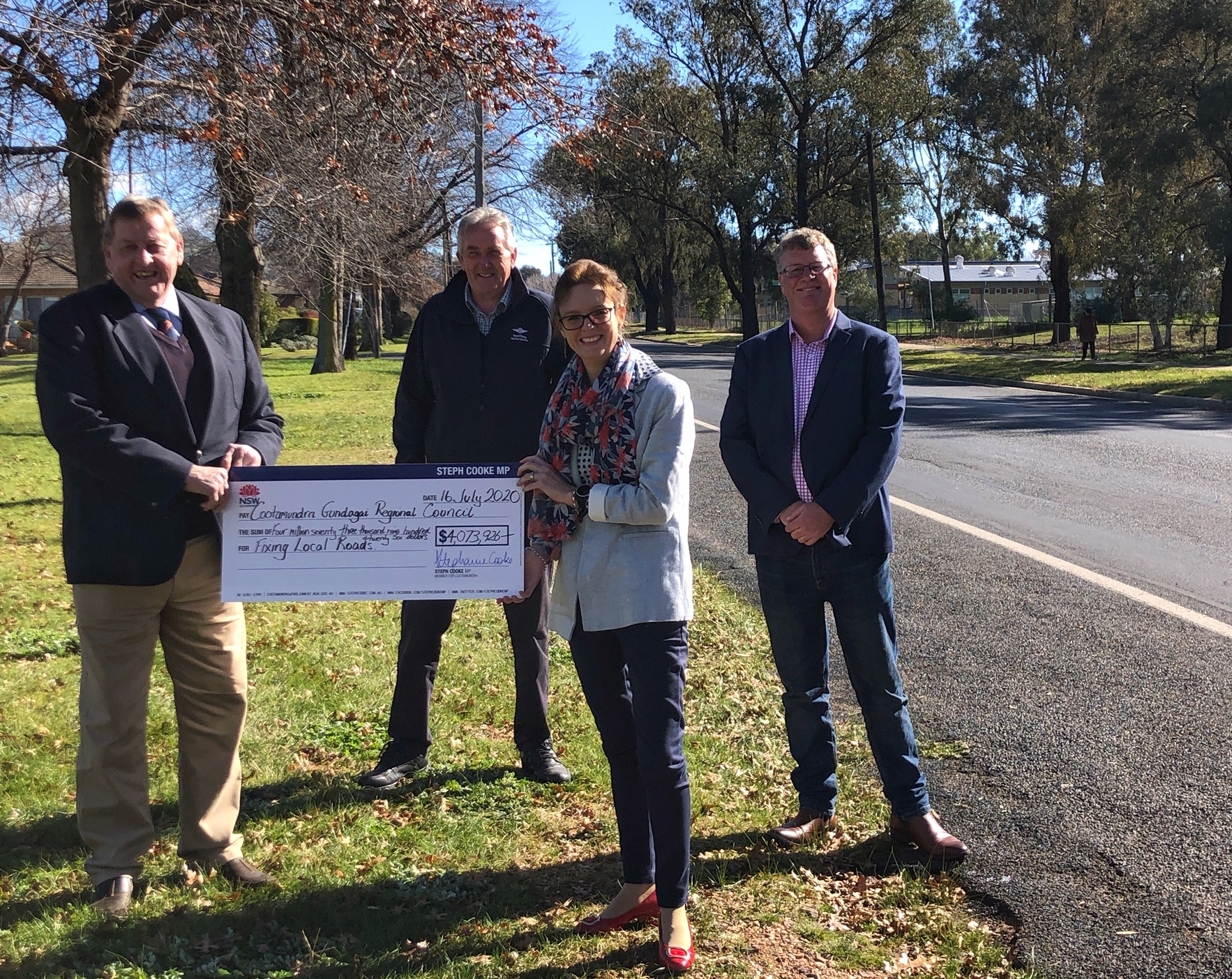 Steph Cooke and Mayor Abb McAllister hold a large cheque and smile at the camera. They stand on the side of a road.