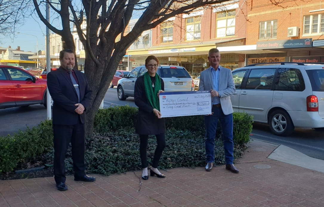 Hilltops Council GM Anthony O'Reilly, Steph Cooke MP and Mayor Brian Ingram hold a large cheque and stand beside the main street in Young.