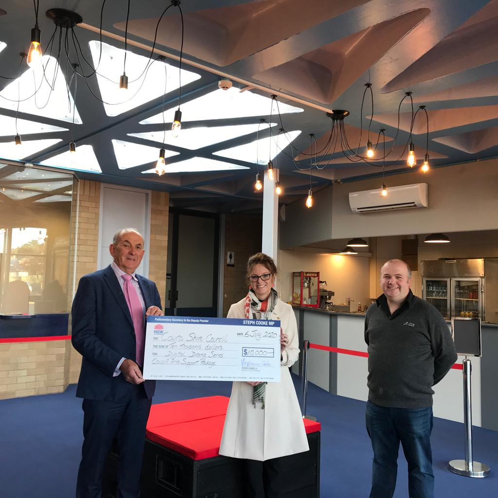 Mayor Bill West, Steph Cooke and Cowra Civic Centre Manager Jonathan Llewellyn stand in the foyer of the Cowra Civic Centre. Bill and Steph hold a large cheque between them.