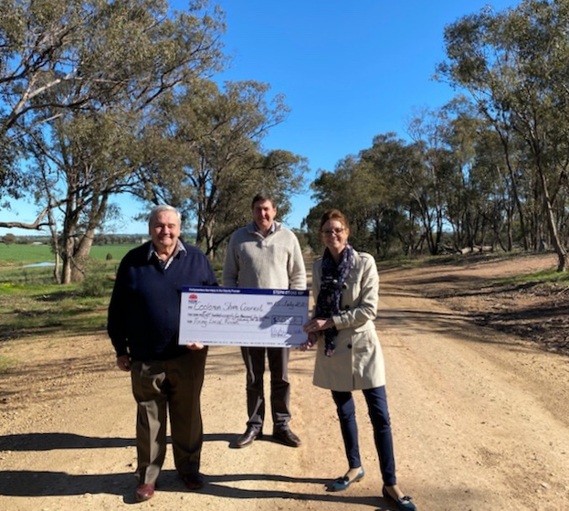Mayor Cr John Seymour, Steph Cooke and Tony Donoghue stand on a dirt road and hold a large cheque.
