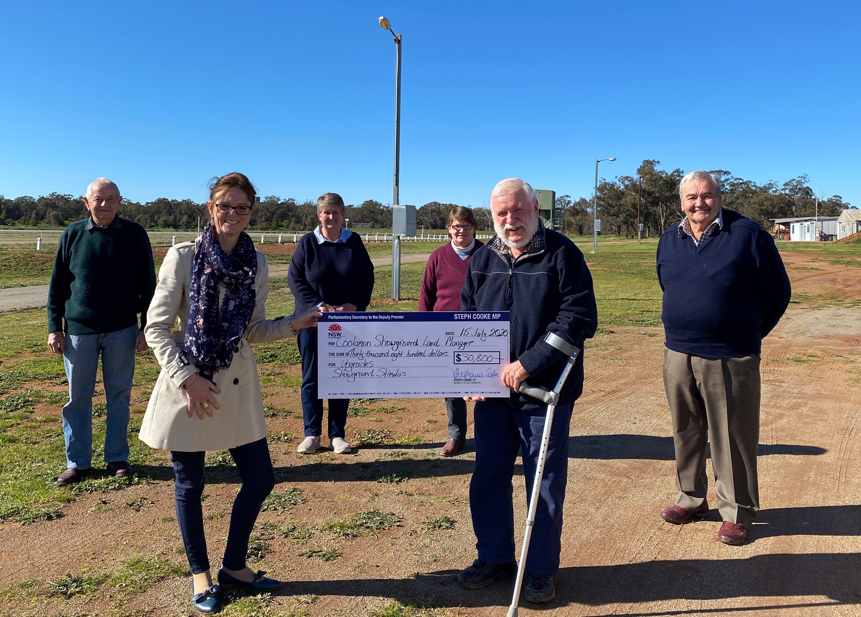Wendy and Peter Dennis, Barry Brill, Steph Cooke MP and Cr John Seymour hold a large cheque at the Coolamon showground.