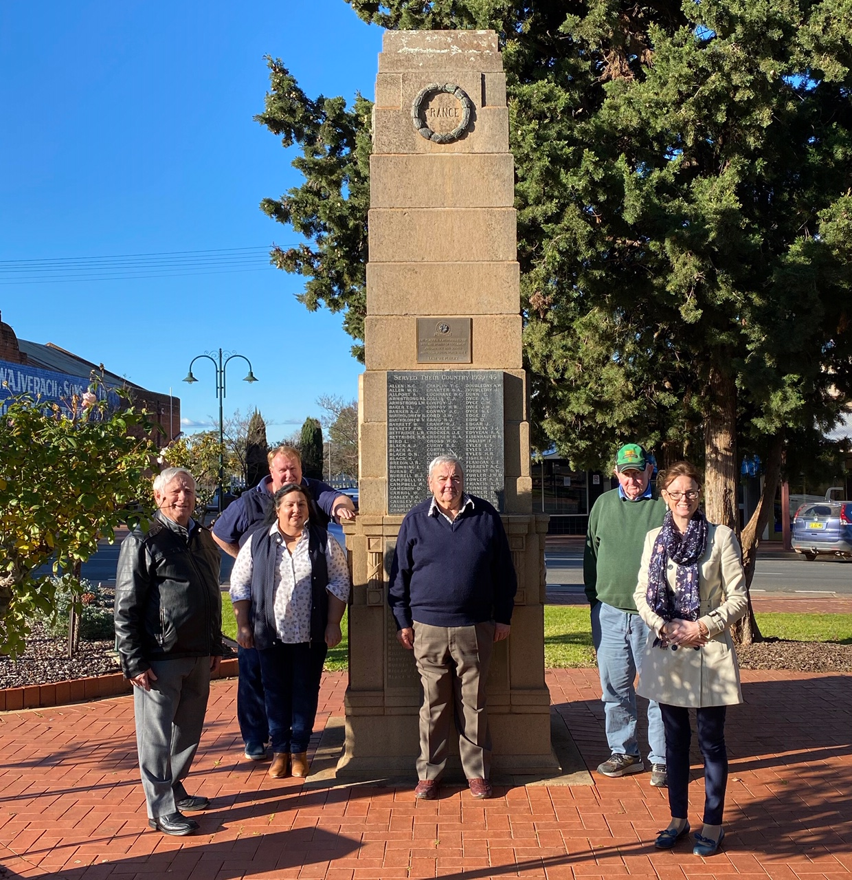 Dave and Angela McCann, Mayor Cr John Seymour, Geoff Glass, Bill Levy and Steph Cooke MP stand in front of the Coolamon cenotaph. The sky is clear and very blue.