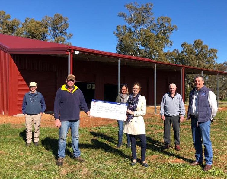 Stephen Hatty, Zane Fraser, Andrew Corbett, Barrie Brill, Catherine Cruikshank and Steph Cooke MP hold a large cheque in front of a new shed.