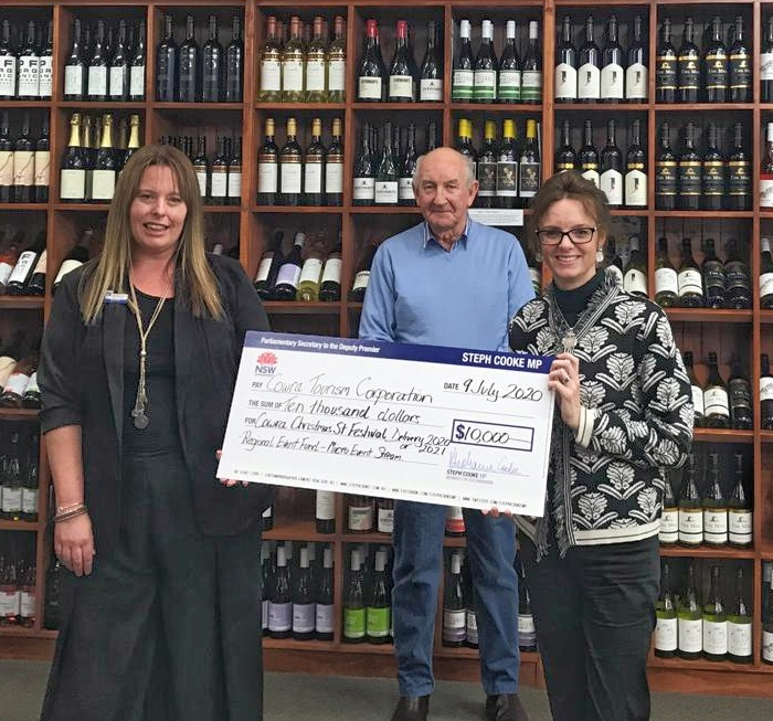 Manager of Cowra Tourism Belinda Virgo, Chair of Cowra Tourism Cr Ray Walsh and Steph Cooke MP hold a large cheque. They stand in front of bottles of local wine.