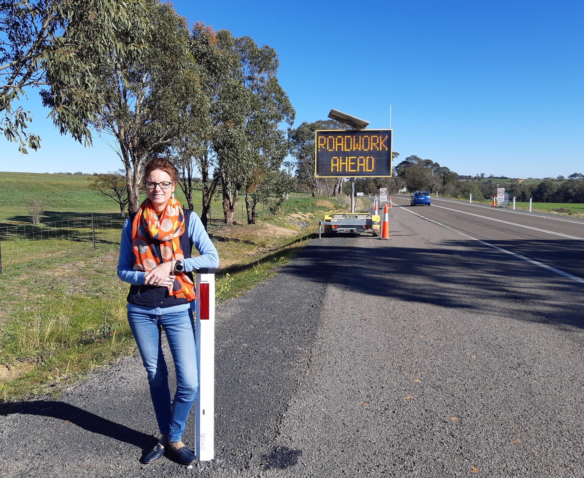 Steph Cooke leans on a guide post and stands beside the Olympic Highway. Behind her is a large sign that says 'Roadwork Ahead'