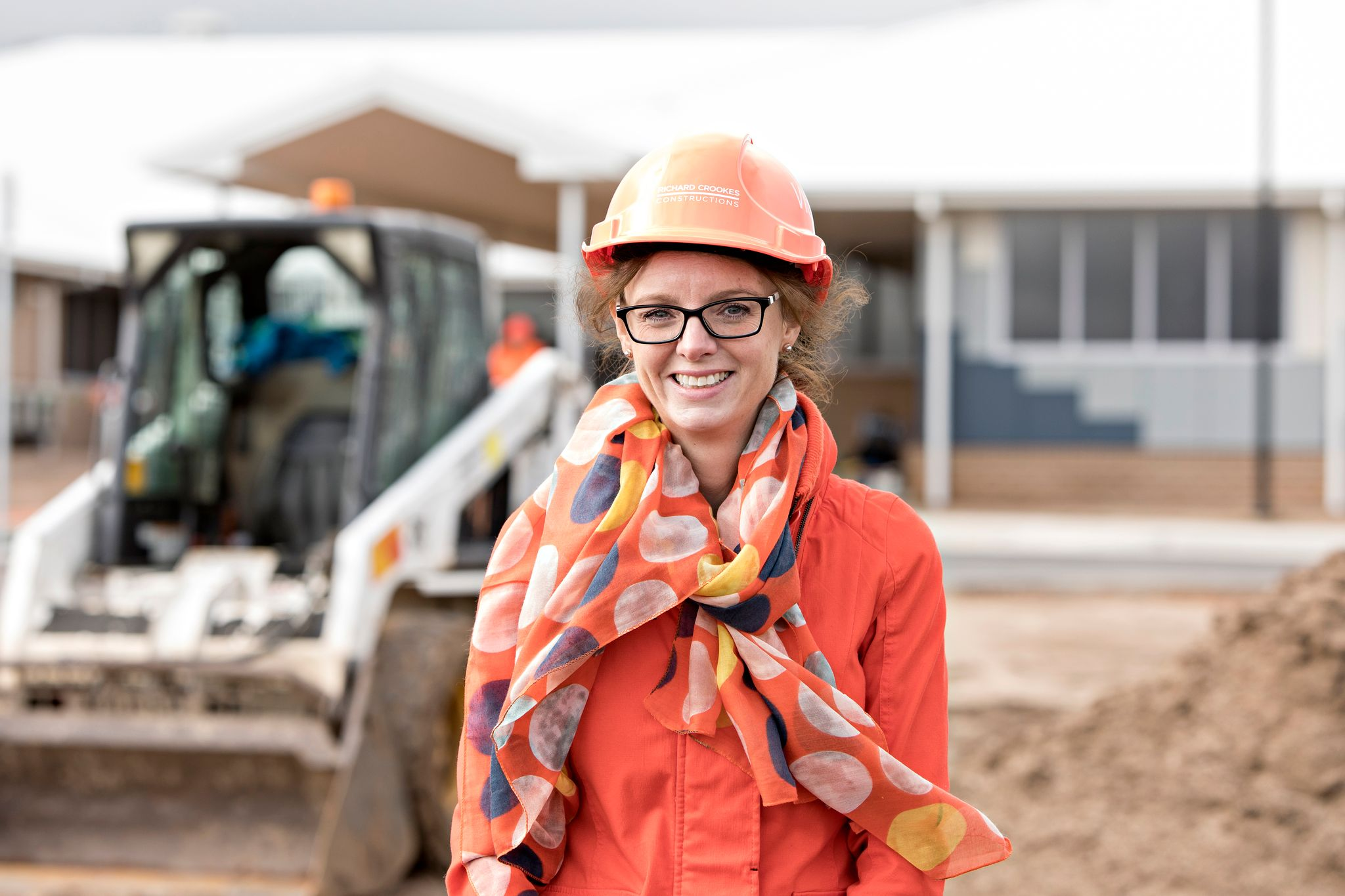Steph Cooke stands at a construction site wearing a hard hat. She smiles at the camera while a bobcat can be seen operating in the background.