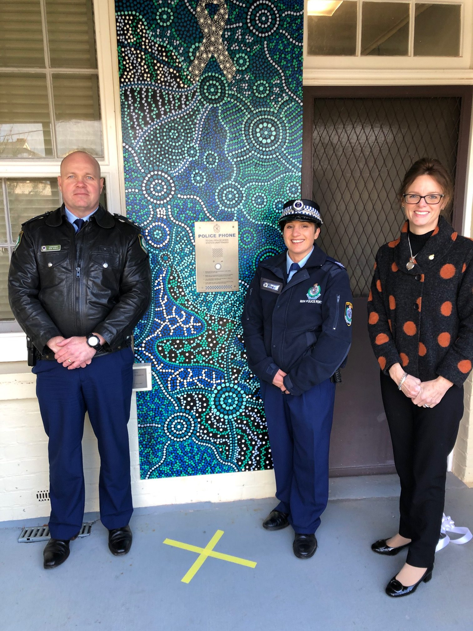 Superintendent Bob Noble, Sergeant Joanne Gallant and Steph Cooke MP stand in front of the blue, black and white indigenous artwork which features a prominent white ribbon