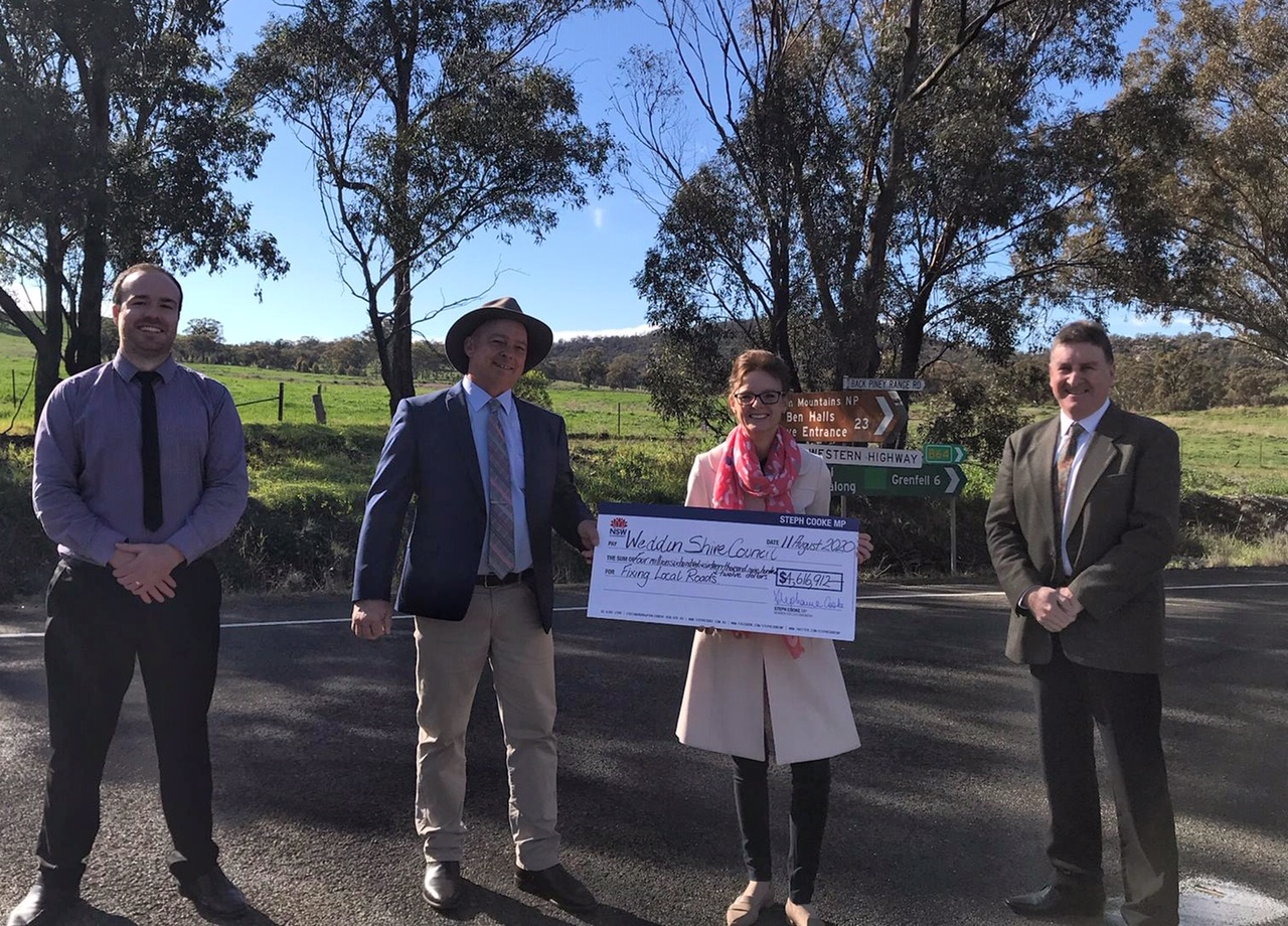 Jaymes Rath, Cr Mark Liebich, Steph Cooke MP and General Manager Glenn Carroll stand on a road and hold a large cheque.