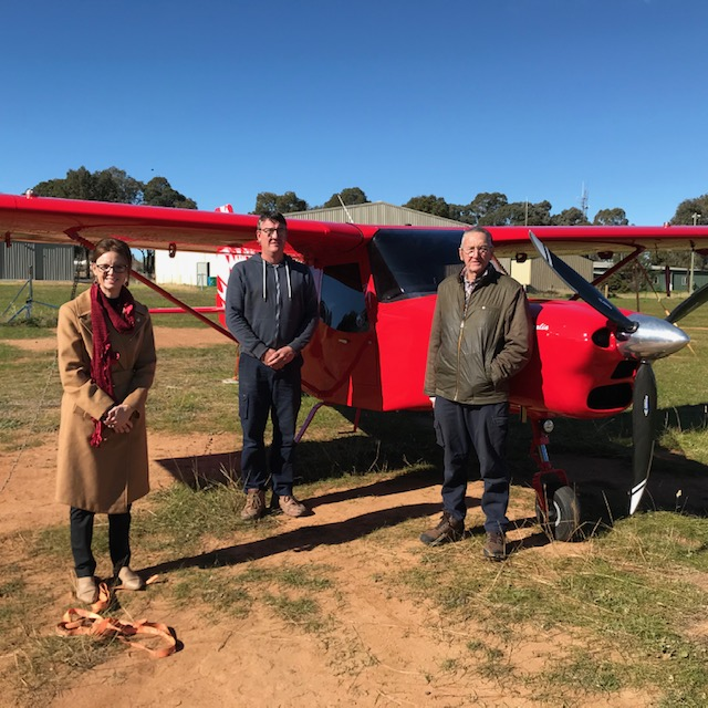 Steph Cooke and two representatives from Brumby Aircraft stand in front of a bright red prop aeroplane.