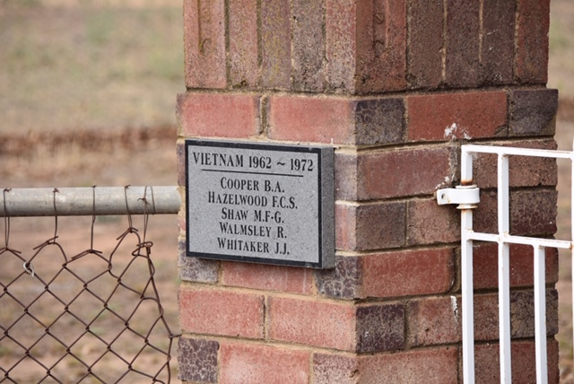 Five names listed on a grey plaque on the brick gates at the Eurongilly War Memorial.